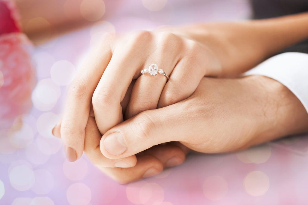 close up of couple hands with engagement ring