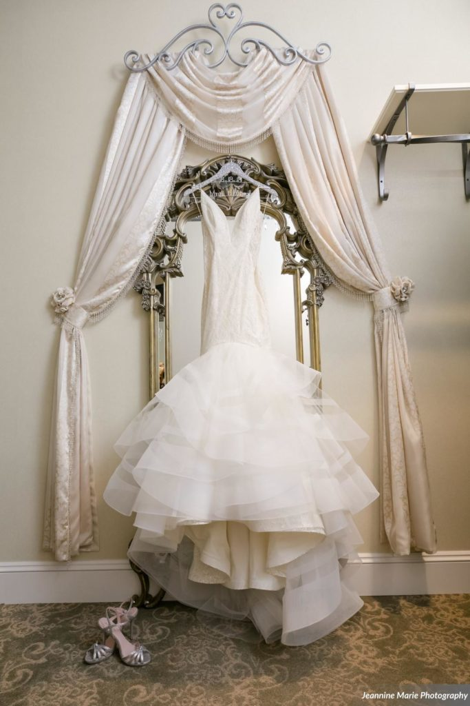 wedding dress hanging in dressing room